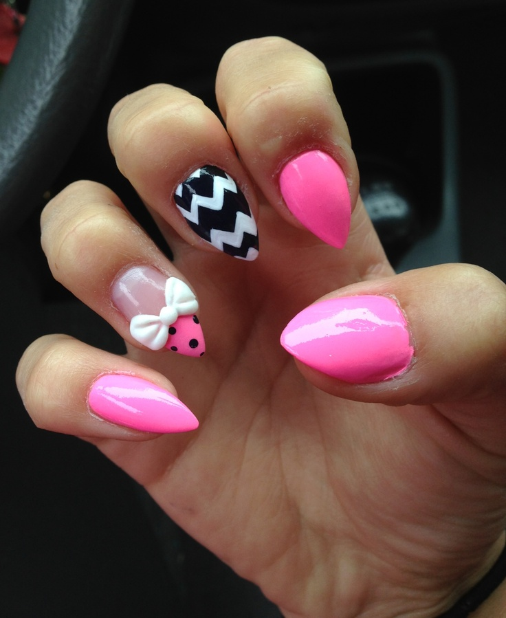Short pink stiletto nails with a 3D acrylic bow and jem cluster