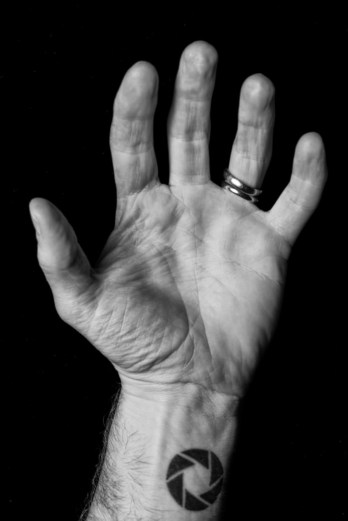 Black and white shot of a man hand with aperture tattoo on the wrist and rings on finger